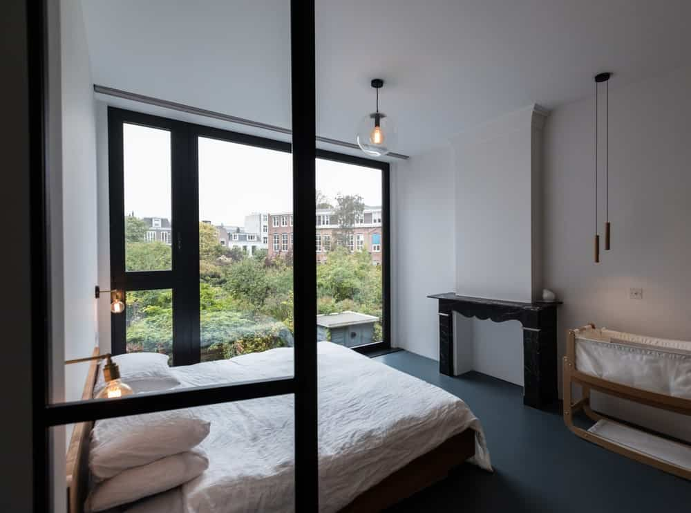 Đây là phòng ngủ chính với sàn màu đen kết hợp tốt với bàn điều khiển, khung giường và khung của các bức tường kính. Chúng tương phản với chiếc giường trắng sáng, tường và trần nhà treo một ánh sáng đơn giản ở giữa.