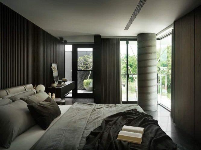 Đây là một phòng ngủ chính tuyệt đẹp và tinh xảo với những bức tường màu đen để phù hợp với những tấm đen của giường và tương phản trần nhà trắng sáng bởi những bức tường kính ở một bên.