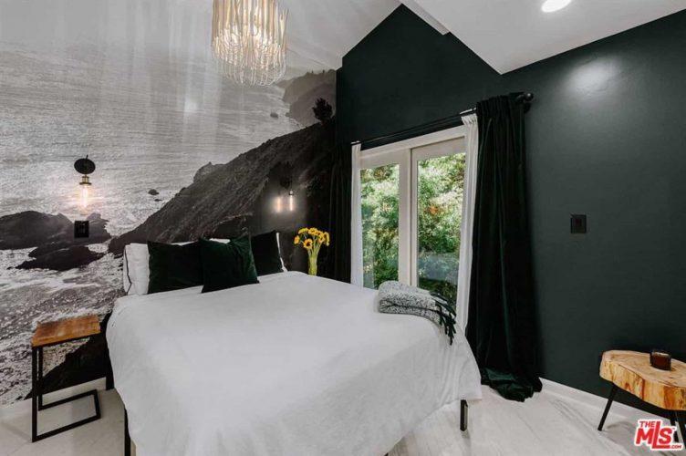 Phòng ngủ này có một bức tường màu đen mờ kết hợp với giấy dán tường màu đen và trắng mô tả một khung cảnh đáng yêu đằng sau chiếc giường trắng kết hợp tốt với sàn và trần nhà màu trắng.