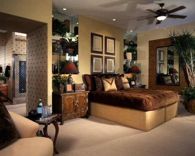 Phòng ngủ nhiệt đới được thiết kế với một tấm gương lớn và khung trưng bày gắn phía trên chiếc giường búi màu nâu. Nó có kệ kính và đầu giường bằng gỗ đứng đầu với đèn bàn.
