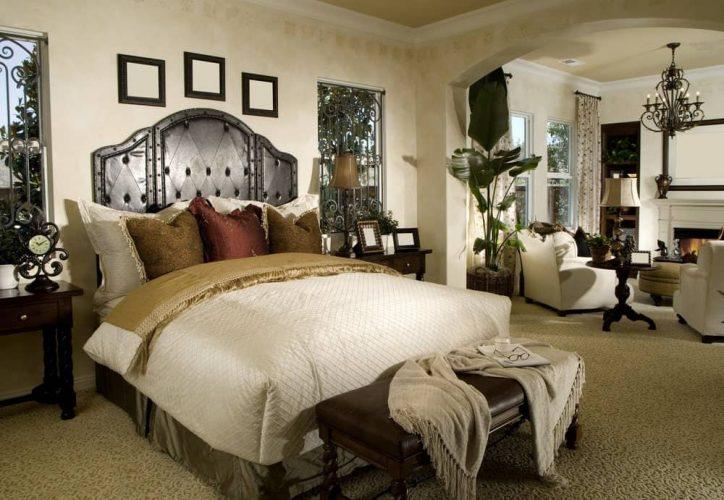 Một chiếc ghế da màu nâu nằm trước giường ngủ trong phòng ngủ chính này có khu vực tiếp khách bên lò sưởi được thắp sáng bởi đèn sàn truyền thống và đèn chùm trang trí công phu.