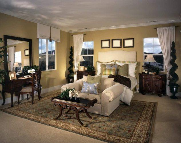 Đầu giường bằng gỗ chạm khắc đặt cạnh một chiếc giường màu be với một chiếc giường tình yêu ở cuối cùng với một bàn cà phê bằng gỗ tối màu. Phòng này có một tấm thảm trang điểm và cổ điển nằm trên sàn thảm.