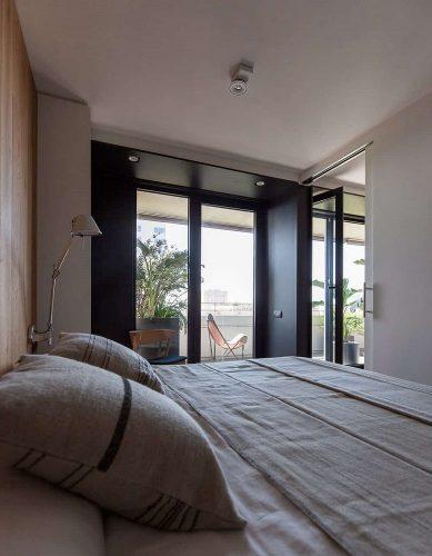 Phòng ngủ này có những bức tường trắng sáng được chiếu sáng bởi ánh sáng tự nhiên đến từ cửa ban công kính.  Những cánh cửa này có khung màu đen nổi bật trên nền tường và trần nhà màu trắng.