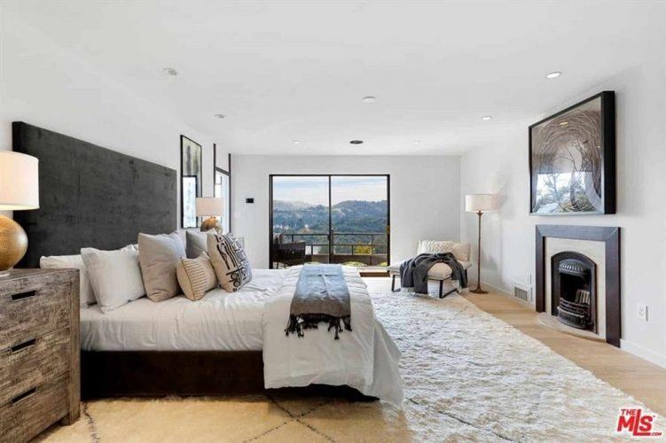 Phòng ngủ chính này có một tấm thảm màu trắng gần như bao phủ sàn gỗ cứng.  Điều này làm cho khung giường màu đen nổi bật cũng như lớp phủ màu đen của lò sưởi và chiếc ghế ở góc cạnh cửa ra ban công.