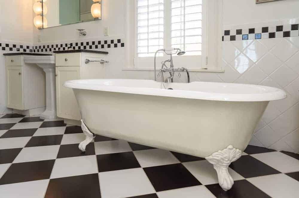 Bồn tắm trắng được đặt dưới cửa sổ với cửa chớp trắng để mang lại ánh sáng tự nhiên.