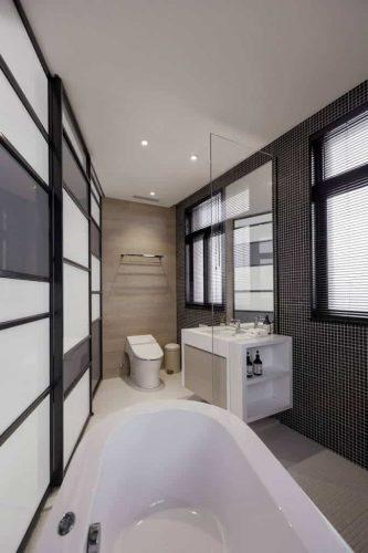 Phòng tắm được lấp đầy với các chi tiết sắc nét, bao gồm sàn và tường vi gạch, với một bồn ngâm lớn chia sẻ không gian với một bàn trang điểm nổi màu trắng táo bạo.