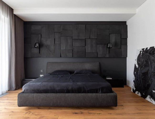Phòng ngủ đẹp này có một chiếc giường màu đen với đầu giường màu đen để phù hợp với bức tường màu đen kết cấu đằng sau nó.  Chúng sau đó được bổ sung bởi sàn gỗ cứng và trần và tường màu trắng sáng ở bên cạnh.