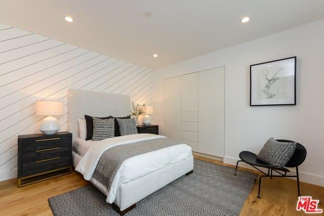 Các bức tường và trần nhà màu trắng sáng của phòng ngủ này phù hợp hoàn hảo với tông màu sáng của chiếc giường. Sau đó, chúng được tạo điểm nhấn bằng các yếu tố màu đen khác nhau như gối, ngăn kéo đầu giường và ghế đối diện với chân giường có một tấm thảm màu xám.