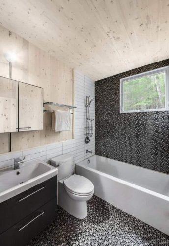 Phòng tắm đánh dấu một sự khởi đầu phong cách cho ngôi nhà, tràn ngập những viên gạch siêu nhỏ màu xám và hoa văn tường gạch trắng.