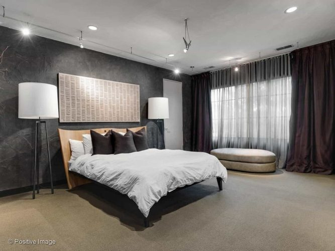 Đây là một phòng ngủ chính thanh lịch với trần nhà màu trắng sáng được tăng cường bởi ánh sáng hiện đại để chiếu sáng những bức tường màu đen bao quanh chiếc giường lớn với một tấm vải trắng.