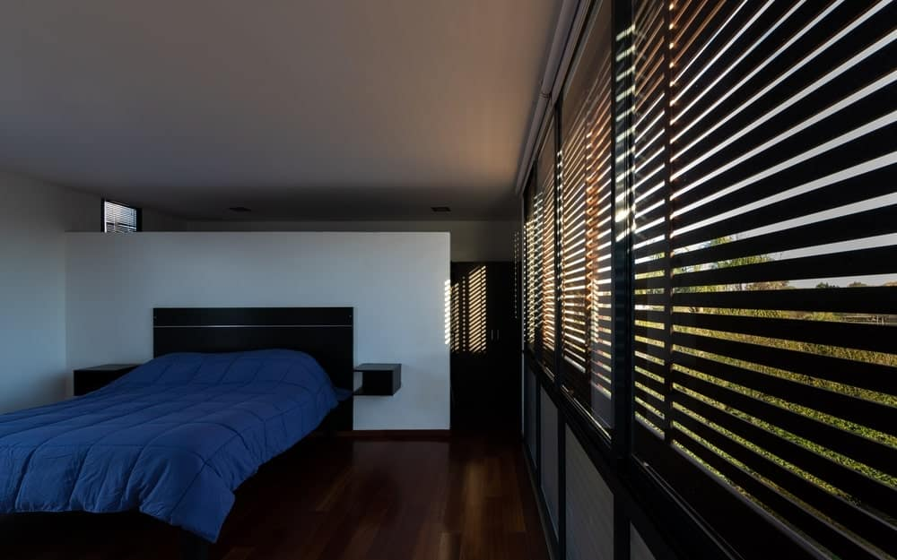 Phòng ngủ tuyệt đẹp này có sàn gỗ cứng tối màu rất phù hợp với khung gỗ màu đen của chuồng và các điểm nhấn của tường và cửa chớp. Chúng nổi bật trên bức tường trắng và trần nhà màu trắng.