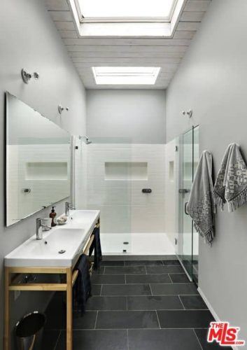 Phòng tắm chính này với bàn trang điểm chìm kép và một chiếc ghế đẩu màu xanh bổ sung cho vòi sen được bao bọc bằng kính.  Nó cũng có một tấm gương lớn trên tường và trần nhà hình vòm cao.