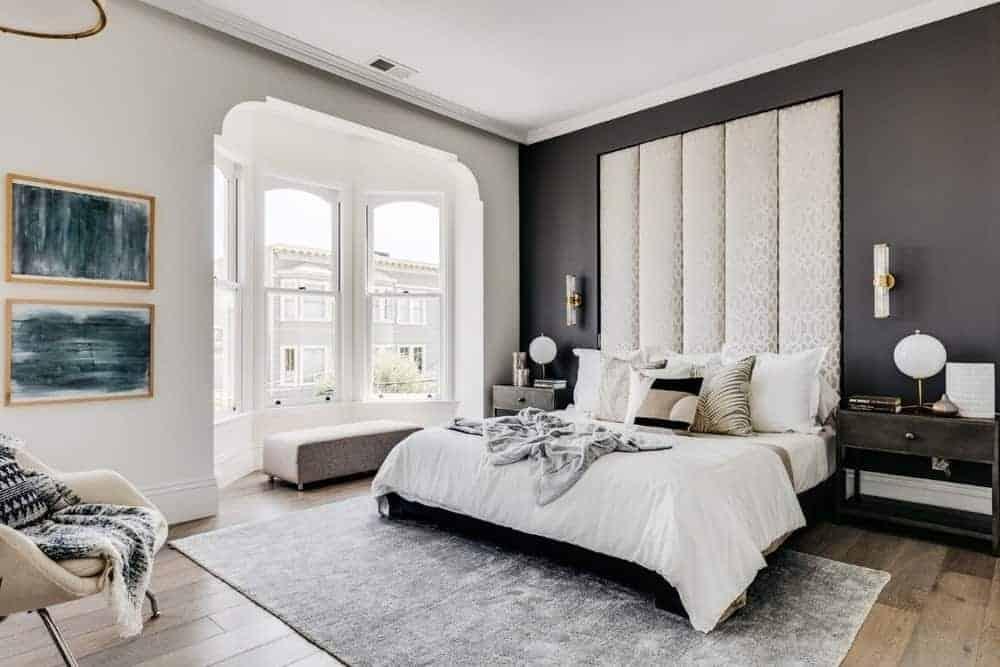 Phòng ngủ chính này có một chiếc giường thoải mái trên tấm thảm và những bức tường màu đen phù hợp với trần nhà màu trắng.