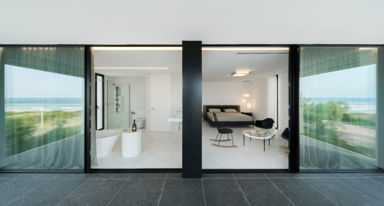 Đây là khung cảnh của phòng ngủ và phòng tắm từ ban công.  Ở đây bạn có thể thấy phòng ngủ xinh xắn ở phía bên phải với một chiếc giường màu đen hiện đại để phù hợp với những chiếc ghế ở khu vực ngồi.  Chúng nổi bật trên sàn nhà, tường và trần nhà màu trắng sáng.