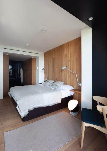 Phòng ngủ chính ấm cúng với ghế đệm và giường ngủ được bổ sung bởi đầu giường tích hợp cố định trên các bức tường ốp gỗ.  Có tủ quần áo đối diện ở bên cạnh phòng tắm kín kính.