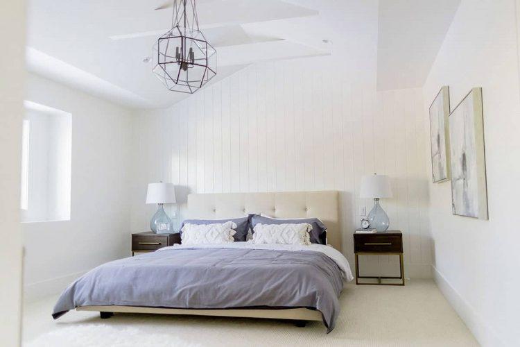 Phòng ngủ chính sáng sủa này trưng bày một chiếc giường búi màu be và đầu giường bằng gỗ tối màu với đèn bàn bằng kính. Nó được trang trí với một cặp tác phẩm nghệ thuật phù hợp và một đèn chùm hình học treo trên trần nhà hình vòm.