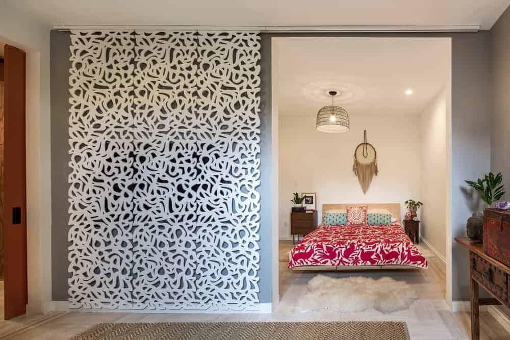 Phòng ngủ chính quyến rũ này trưng bày đồ nội thất bằng gỗ, đèn chùm vòm, dreamcatcher và tấm thảm lông mịn trên sàn gỗ cứng nhẹ.  Căn phòng được bao bọc trong một cánh cửa trượt đầy phong cách được thiết kế với các chi tiết phức tạp.