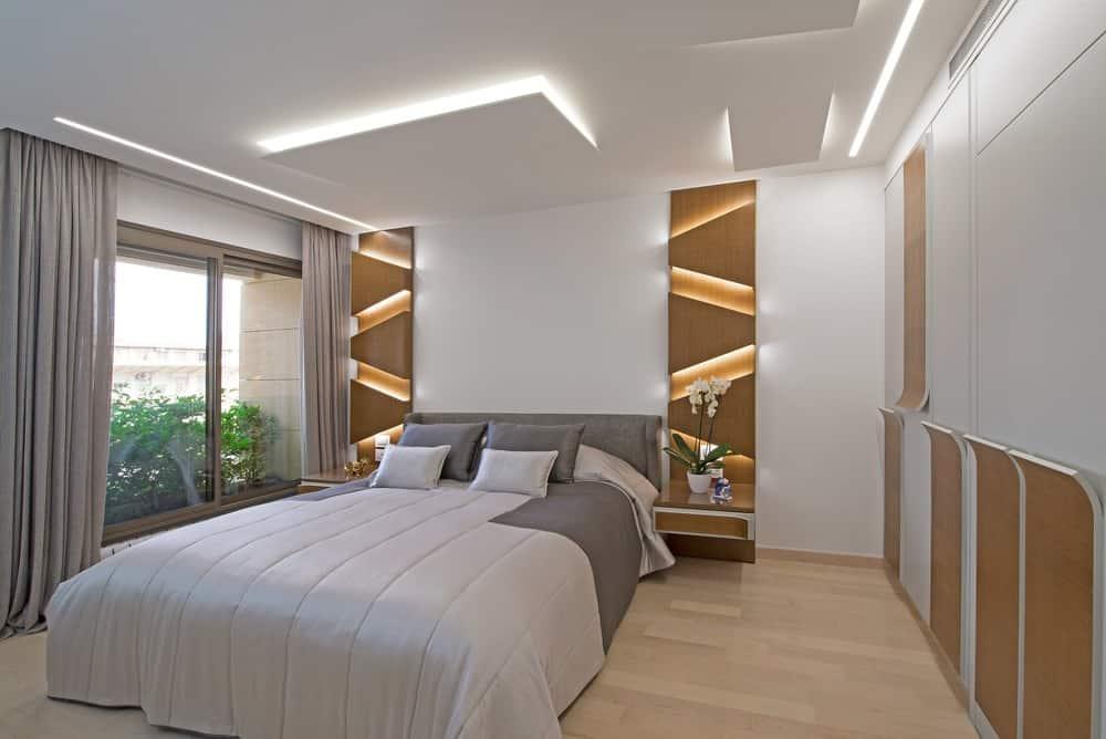 Những tấm gỗ phát sáng đặt một phông nền tuyệt đẹp trong phòng ngủ chính này với sàn gỗ cứng và cửa sổ trượt bằng kính được phủ trong rèm màu xám. Nó có một chiếc giường thoải mái bên cạnh đầu giường tích hợp.