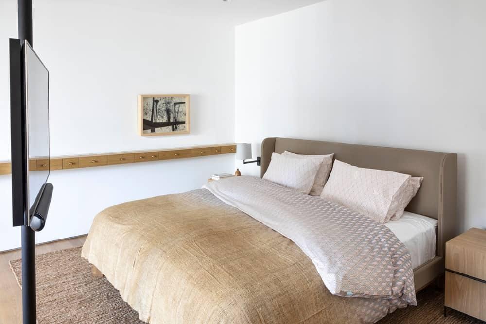 Phòng ngủ chính này cung cấp đầu giường bằng gỗ và giường có cánh phía sau ngồi trên tấm thảm có họa tiết màu be. Có một cái cột ở bên cạnh giữ TV màn hình phẳng.