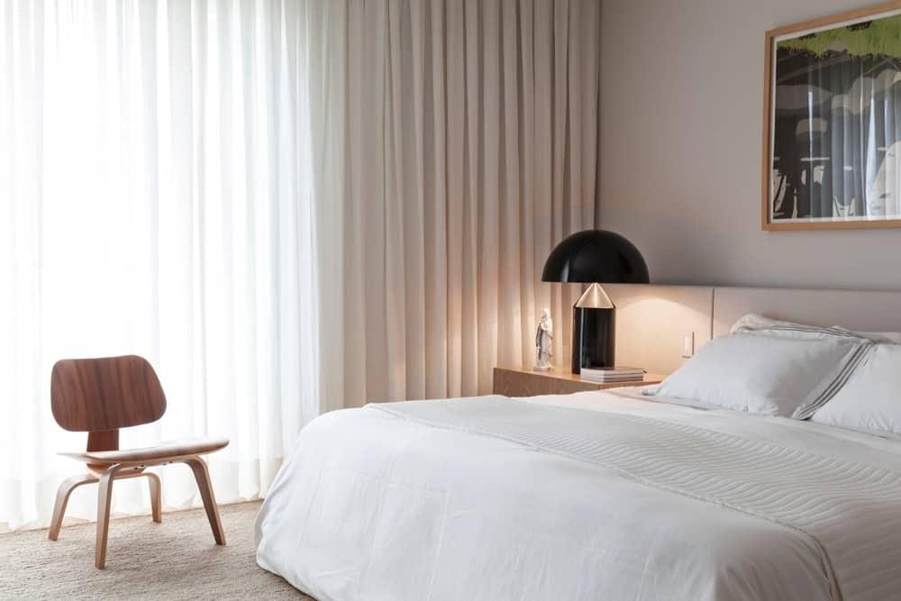 Một phòng ngủ chính ấm cúng được trang trí với một chiếc đèn bàn sành điệu và một tác phẩm nghệ thuật thú vị được gắn phía trên chiếc giường trắng. Nó cung cấp một chiếc ghế gỗ nằm đối diện với các cửa sổ chiều cao đầy đủ được bao phủ trong rèm cửa tuyệt đối.