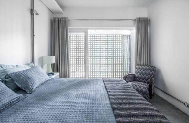 Phòng ngủ chính kiểu công nghiệp được trang bị giường thoải mái và ghế bành chevron đặt trước tấm rèm màu xám. Phòng có sàn lát gạch bê tông và những bức tường trắng trơn với những đường ống lộ ra.