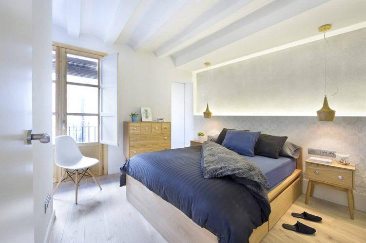 Phòng ngủ chính này trưng bày mặt dây chuyền bằng gỗ và đồ nội thất kết hợp với sàn gỗ rộng.  Nó có trần nhà với xà ngang màu trắng và một cánh cửa kiểu Pháp mở ra ban công.