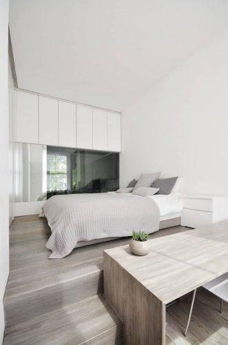 Một phòng ngủ chính được thiết kế thông minh có giường ngủ nằm trên bục được tích hợp với bàn phù hợp.  Nó có một đầu giường màu trắng và tủ tích hợp nằm phía trên bức tường gương.