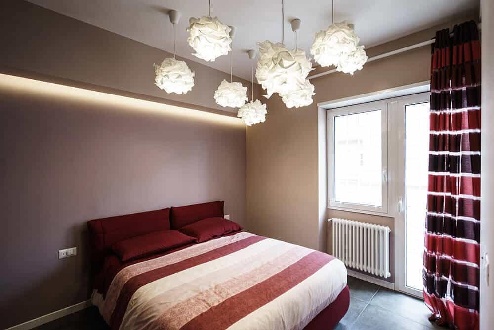 Phòng ngủ chính này được thiết kế với ánh sáng hoa độc đáo gắn trên trần nhà màu trắng thông thường. Nó có những tấm rèm nổi bật bổ sung cho chiếc giường màu đỏ tía được phủ trong một chiếc chăn sọc.