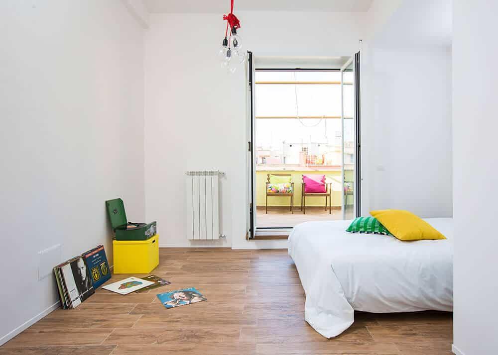 Phòng ngủ chính tối giản với sàn gỗ cứng và giường trắng phản chiếu những bức tường nguyên sơ.  Nó bao gồm một cánh cửa kiểu Pháp dẫn ra ban công đầy những chiếc ghế ấm cúng.