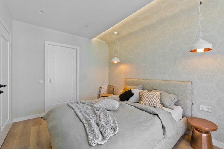Một hình nền hoa văn đặt một phông nền đẹp cho giường nền màu xám được chiếu sáng bởi mặt dây chuyền vòm màu trắng.  Nó được bao quanh bởi một bàn bên cạnh và một chiếc ghế gỗ kết hợp với sàn gỗ cứng.