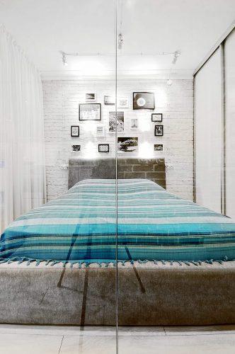 Một phòng ngủ nhỏ được thiết kế với khung phòng trưng bày gắn trên bức tường gạch trắng. Hàng dệt sọc nổi bật trên bức tường trắng và rèm cửa tuyệt đối.