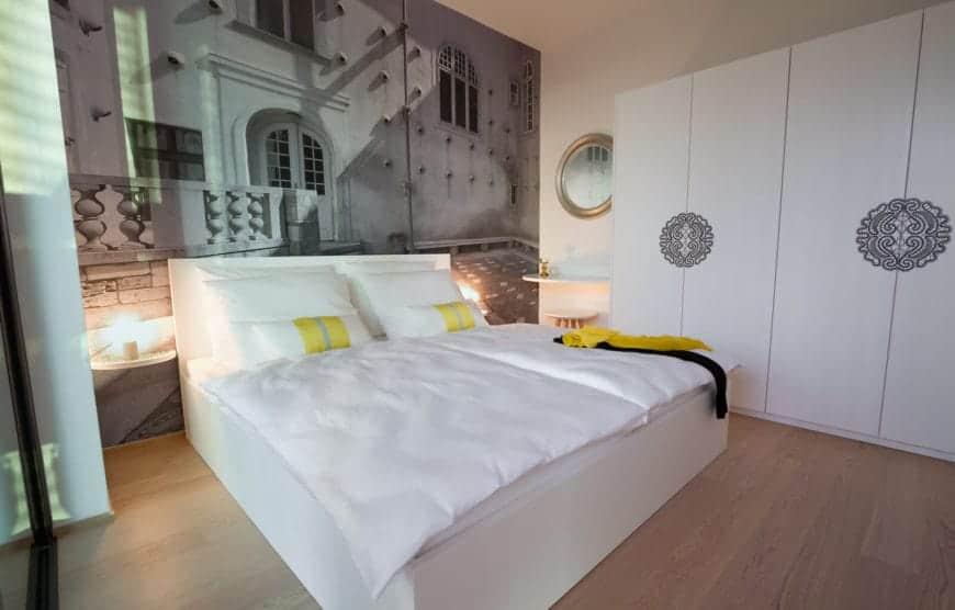 Phòng ngủ chính hiện đại được thiết kế với một bức tranh tường tuyệt đẹp và tay cầm trang trí được trang bị trên tủ quần áo tối giản. Điểm nhấn màu vàng tinh tế tương phản với chiếc giường trắng bóng mượt.