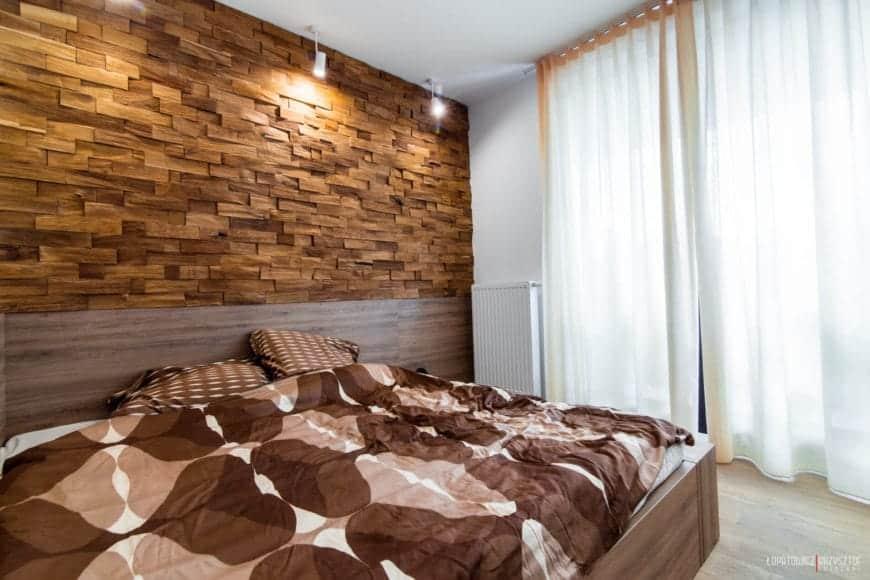 Phòng ngủ chính có giường khung gỗ lớn, nhiều lớp kính ngoài từ sàn đến trần để lấy ánh sáng tự nhiên và bề mặt tường gạch gỗ độc đáo được chiếu sáng bởi các nguồn sáng tập trung.