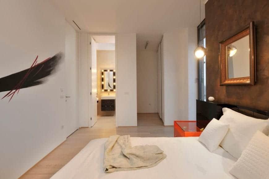 Phòng ngủ chính màu trắng có phòng tắm riêng nhỏ với cửa kính bên ngoài ở bên phải và yếu tố sơn nghệ thuật trên tường bên trái.