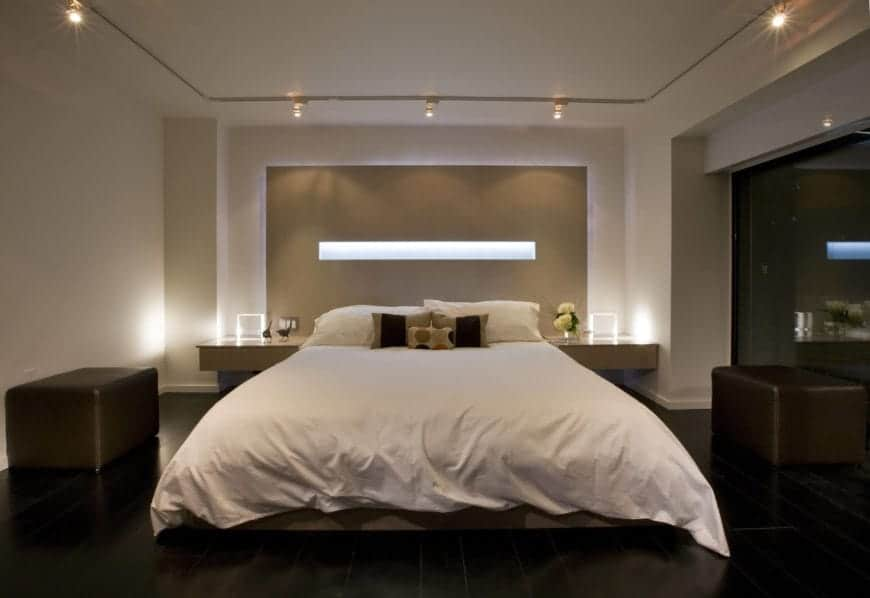 Nhìn từ trên xuống của phòng ngủ chính này trưng bày một chiếc giường phủ màu trắng trước chi tiết bức tường nguyên khối có chứa dải ánh sáng ngang.  Rái cá da lớn màu tối đứng ở mỗi bên.