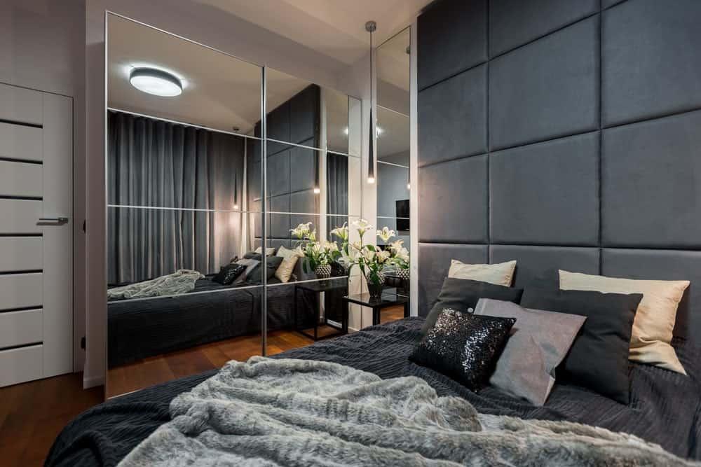 Phòng ngủ chính của căn hộ với sàn gỗ cứng phong phú, gương được ốp và một chiếc giường thoải mái với đầu giường tùy chỉnh lớn.