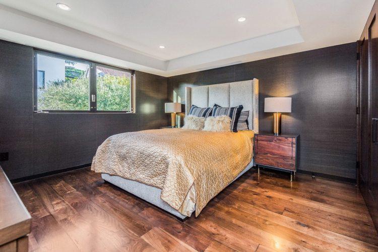 Đây là một phòng ngủ chính thanh lịch đáng yêu với những bức tường màu đen để tương phản với trần khay màu trắng có đèn chiếu sáng. Những điều này làm cho tấm vàng của giường nổi bật.