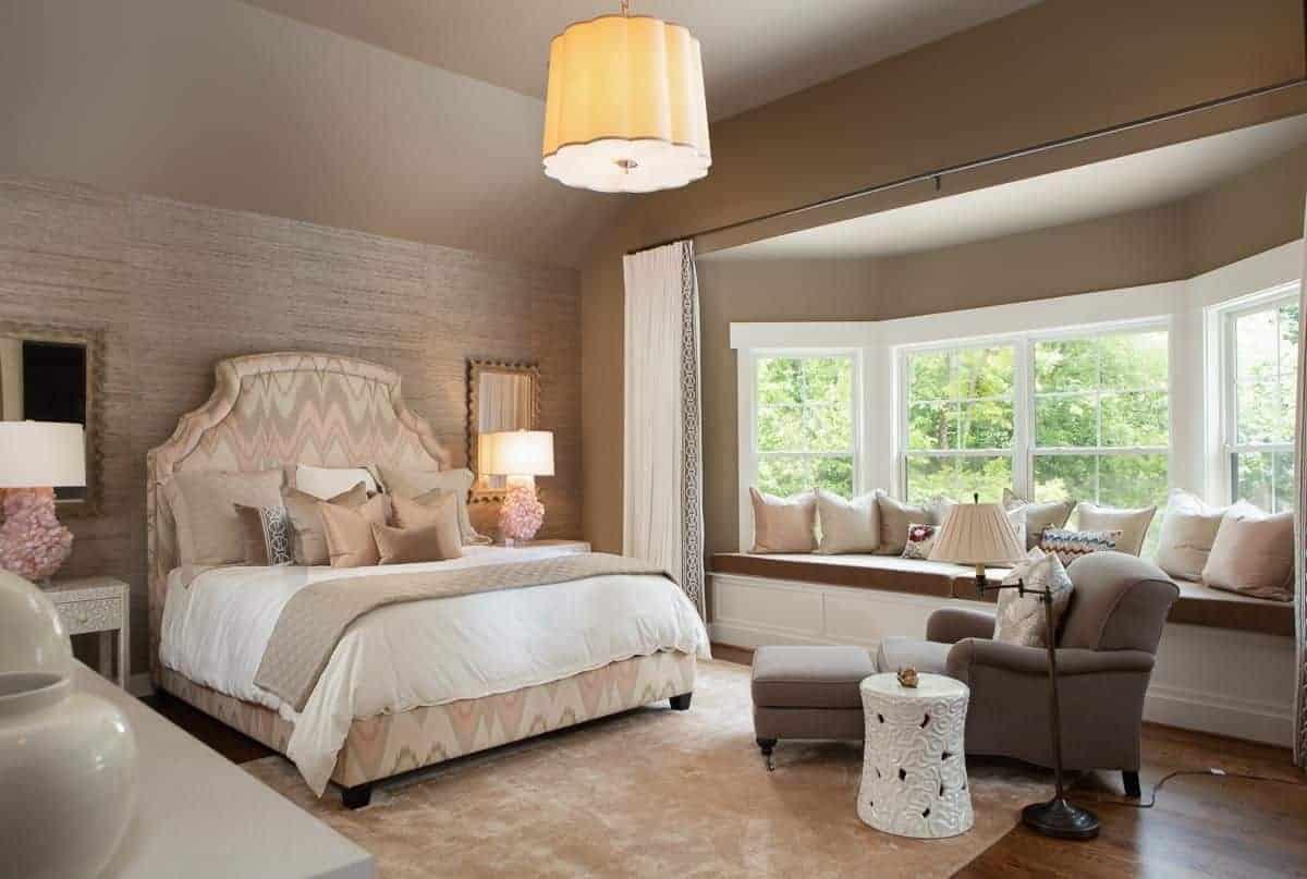 Những chiếc đèn bàn xinh xắn ngồi trên những chiếc đầu giường kiểu dáng đẹp nằm cạnh một chiếc giường duyên dáng đối diện với một chiếc ghế salon taupe với một chiếc bàn tròn. Có một chỗ ngồi bên cửa sổ ở bên cạnh đầy những chiếc gối bông.