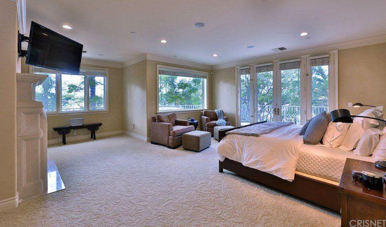 Phòng ngủ chính sáng sủa với sàn trải thảm và cửa sổ bằng kính mang lại nhiều ánh sáng tự nhiên. Nó bao gồm một chiếc giường gỗ và ghế bành màu nâu kết hợp với ottoman phù hợp.