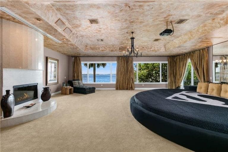 Phòng ngủ chính rộng rãi có lò sưởi hiện đại và giường tròn lớn với gương không khung ở trên.  Nó có trần khay và cửa sổ ốp kính nhìn ra khung cảnh đại dương tuyệt đẹp.