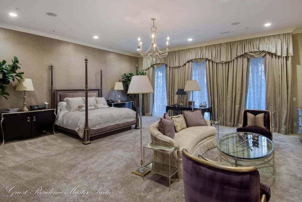 Phòng ngủ chính Địa Trung Hải với giường bốn cọc và khu vực tiếp khách được thắp sáng bởi đèn chùm nến và đèn trần âm trần.  Nó có thảm trải sàn và cửa sổ chiều cao đầy đủ được phủ bằng màn và diềm sang trọng.