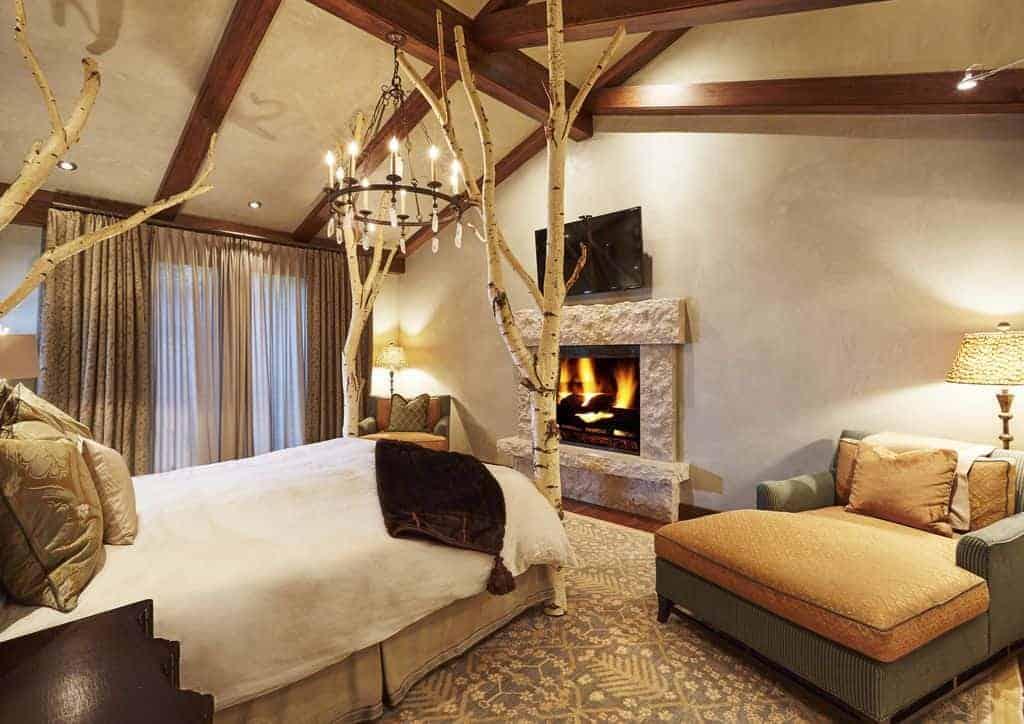 Một TV màn hình phẳng treo phía trên lò sưởi bê tông trong phòng ngủ mộc mạc này với một chiếc giường cây tráng lệ và những chiếc ghế ấm cúng được chiếu sáng bởi một đèn chùm sắt rèn và đèn sàn ấm áp.