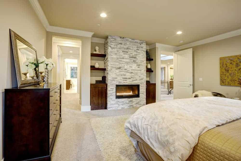 Phòng ngủ chính này trưng bày một chiếc giường thoải mái và lò sưởi bao quanh bằng kính được trang bị trên cột gạch.  Nó bao gồm kệ tích hợp và tủ gỗ tối màu đứng đầu với gương và bình hoa thủy tinh.
