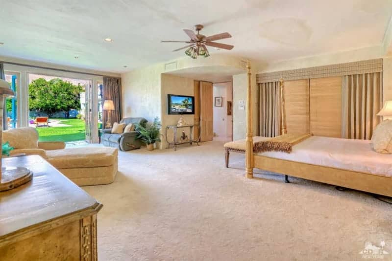 Một chiếc giường bốn cọc đối diện với bàn điều khiển trên cùng bằng kính và TV treo tường trong phòng ngủ chính màu be này với sàn trải thảm và cửa đôi bằng kính dẫn ra sân xanh tươi tốt.