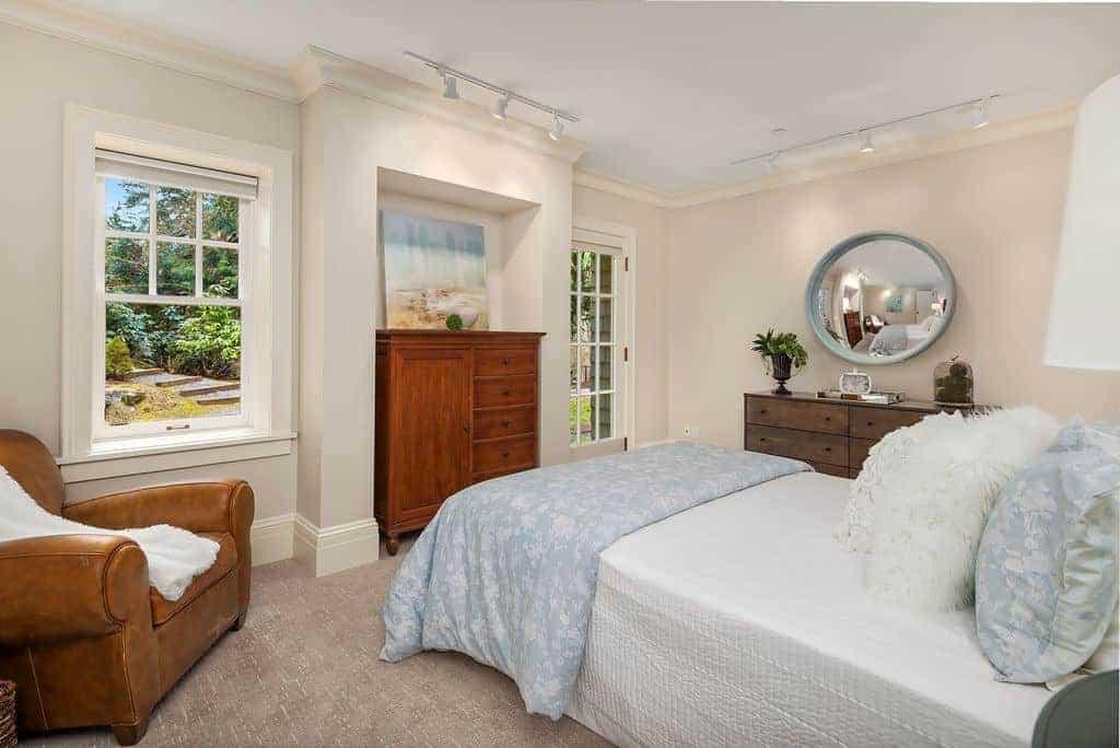 Phòng ngủ thoáng mát được trang trí với gương lõm tròn và tác phẩm nghệ thuật đáng yêu được chiếu sáng bởi đèn đường trắng.  Nó có một chiếc ghế bành bọc da màu nâu và một chiếc giường thoải mái với đầy những chiếc gối lông và lông.
