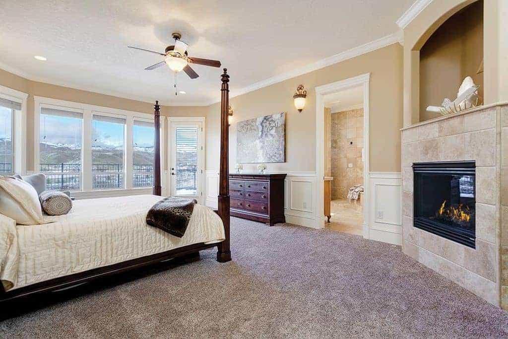 Phòng ngủ chính tinh xảo với thảm trải sàn và cửa sổ ốp kính mời ánh sáng tự nhiên vào. Nó bao gồm một lò sưởi hiện đại và bốn giường poster bổ sung cho tủ gỗ.