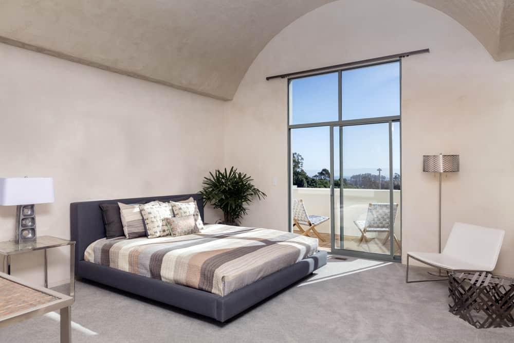 Một chiếc ghế màu trắng bóng bẩy đối diện với chiếc giường bục màu xám trong phòng ngủ chính này với trần hình vòm và một thanh trượt bằng kính mở ra ban công đầy những chiếc ghế bấc.