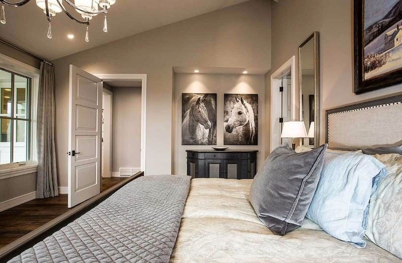 Phòng ngủ chính sang trọng có giường ấm cúng được lót một tấm chăn màu xám.  Có một bàn điều khiển bằng gỗ tối màu ở bên cạnh được tạo điểm nhấn bằng những bức tranh ngựa gắn trên tường.