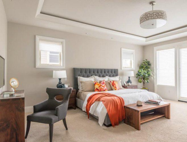 Một chậu cây xanh tạo ra bầu không khí sảng khoái trong phòng ngủ chính màu be này với đầu giường bằng gỗ và một chiếc giường bập bênh bổ sung cho chiếc ghế bành màu xám.