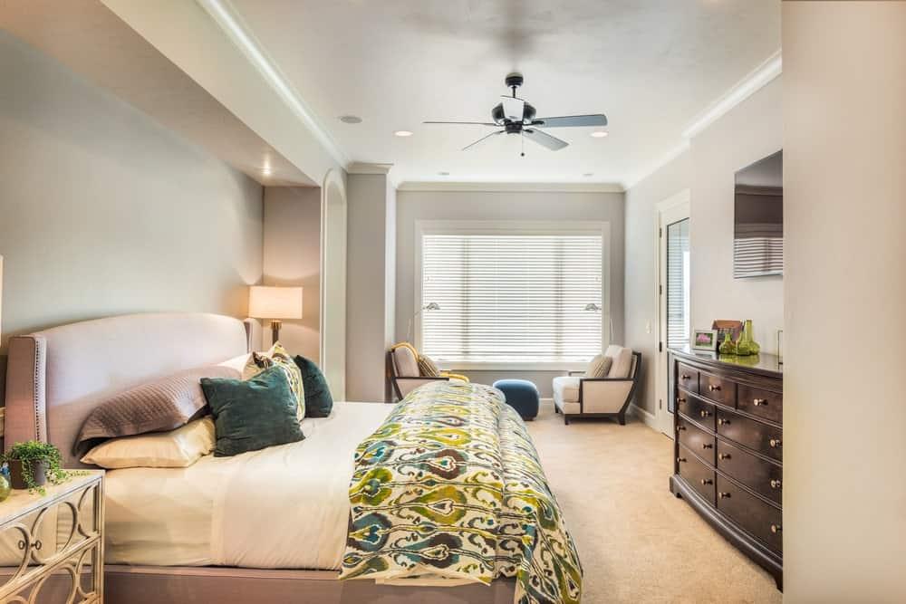 Phòng ngủ chính tươi mới trưng bày khu vực tiếp khách và giường bọc nệm đối diện với tủ gỗ và gương không khung.  Nó có sàn thảm và trần nhà thường xuyên được gắn với quạt và đèn chiếu sáng.